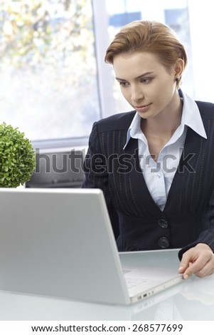 Elegant young businesswoman sitting at desk, working with laptop. - stock photo