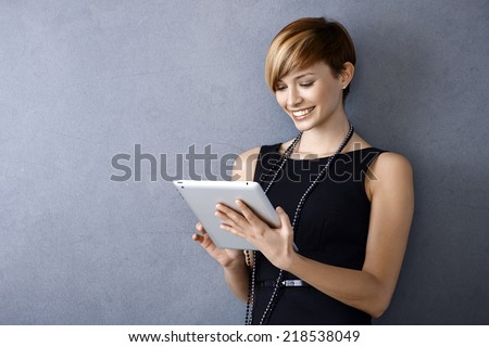 Elegant young businesswoman using tablet leaning to wall, looking at screen - stock photo