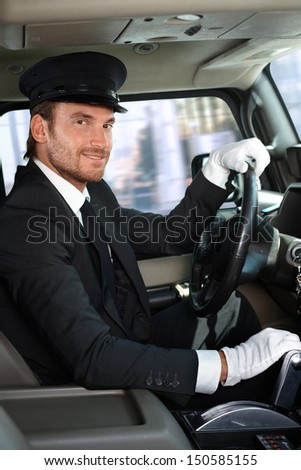 Elegant young chauffeur driving limousine, smiling.