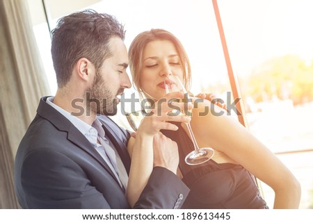 Elegant Young Couple Cheering at Hotel Suite - stock photo