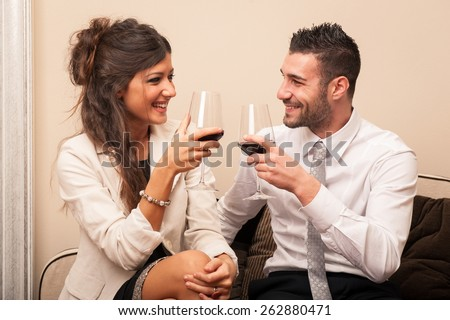 Elegant young couple drinking a toast with a glass of wine sit on a sofa. - stock photo