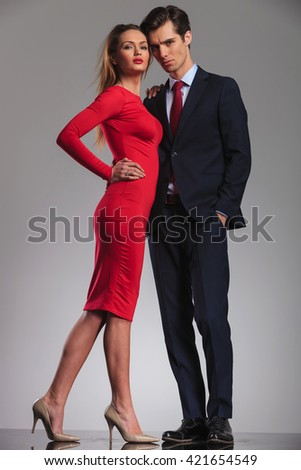 elegant young couple standing embraced in studio, woman in red dress and man in suit and tie