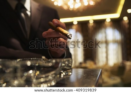 elegant young fashion man in a suit smoking cigar