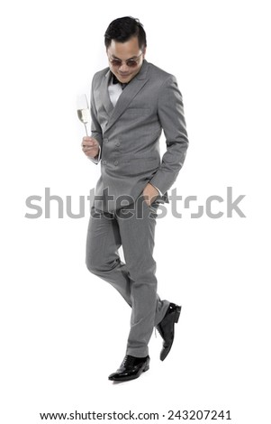 Elegant young fashion man in gray suit raising a glass of champagne on the white background.
