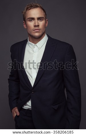 elegant young fashion man in tuxedo looking at the camera while holding his hands on his jacket and a leg behind the other. on gray background - stock photo