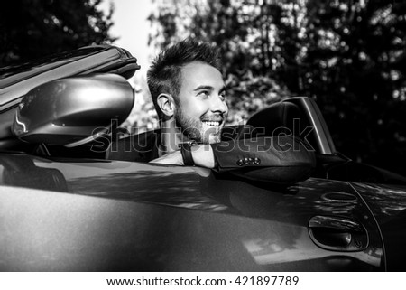 Elegant young fashionable man in convertible car outdoor. Black-white portrait.