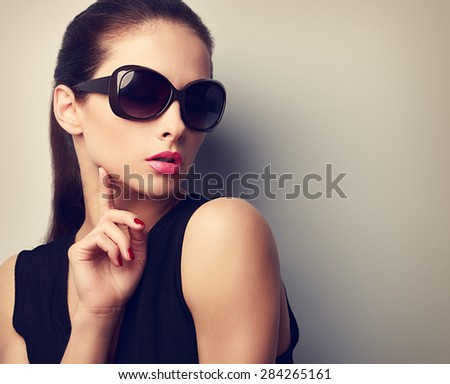 Elegant young female model in trendy sunglasses posing touching hand the face. Vintage closeup portrait with empty copy space - stock photo