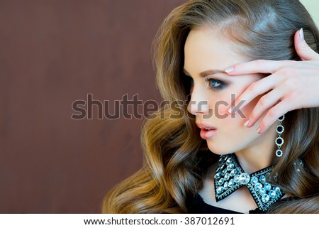 elegant young girl in a black evening dress, with a beautiful hairdress and with smart jewelry poses in an vintage interior. Fashion and beauty shooting. - stock photo