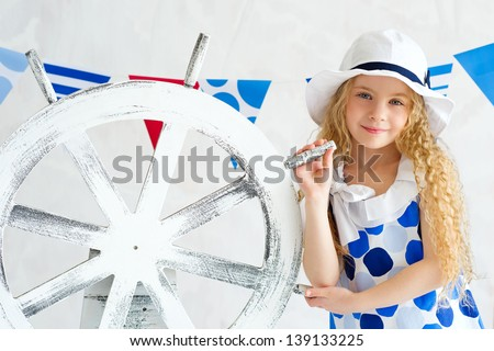 Elegant young girl wearing fashion spotted dress and white hat standing next to decorative wooden steer wheel - stock photo