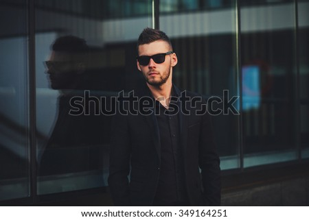 Elegant young handsome business man wearing suit and glasses - stock photo