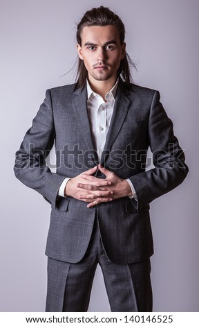Elegant young handsome long-haired man in costume. Studio fashion portrait.  - stock photo