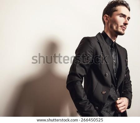 Elegant young handsome man in black costume. Studio fashion portrait.  - stock photo