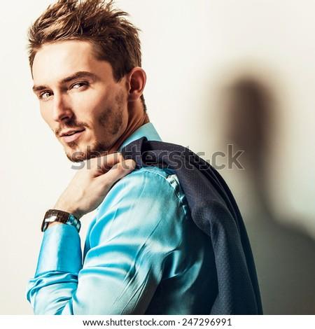 Elegant young handsome man in blue silk shirt & costume. Studio fashion portrait. - stock photo