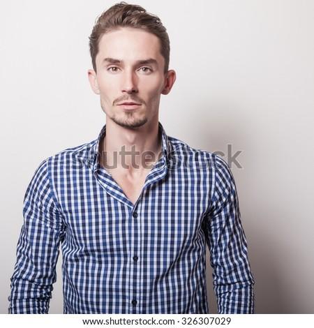 Elegant young handsome man in blue-white shirt. Studio fashion portrait.  - stock photo