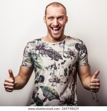 Elegant young handsome man in bright colorful t-shirt. Studio fashion portrait. - stock photo