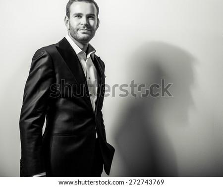 Elegant young handsome man in classic costume. Black-white studio fashion portrait.  - stock photo