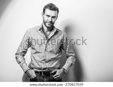 Elegant young handsome man in classic shirt. Black-white studio fashion portrait.