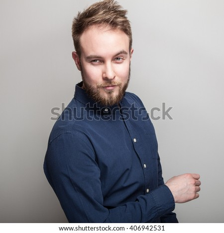 Elegant young handsome man in dark blue classic shirt. Studio fashion portrait. - stock photo