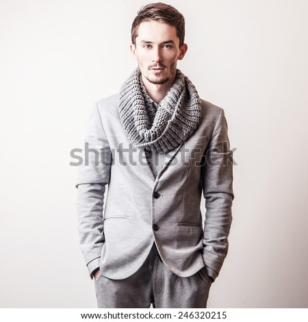 Elegant young handsome man in grey costume. Studio fashion portrait.