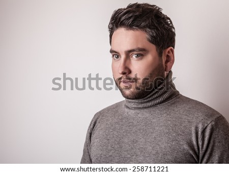 Elegant young handsome man in grey sweater. Studio fashion portrait.