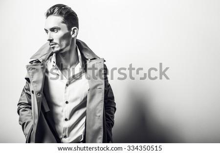 Elegant young handsome man in long stylish coat. Black-white fashion portrait.   - stock photo