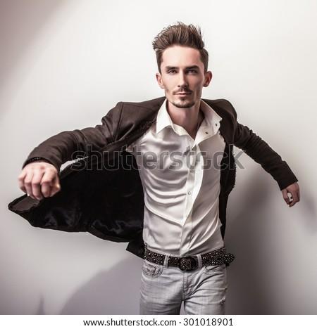 Elegant young handsome man in long stylish coat. Studio fashion portrait.  - stock photo