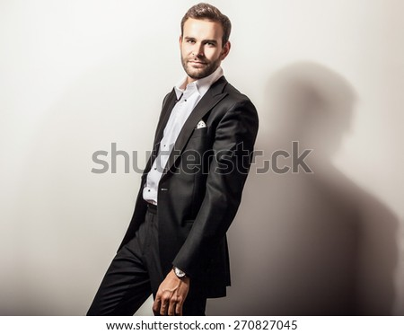 Elegant young handsome man in luxury black costume. Studio fashion portrait.