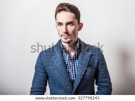 Elegant young handsome man in stylish blue jacket. Studio fashion portrait.  - stock photo
