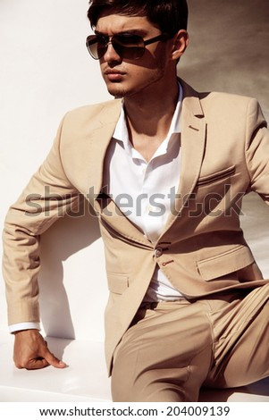 Elegant young handsome man in suite wearing glasses - stock photo