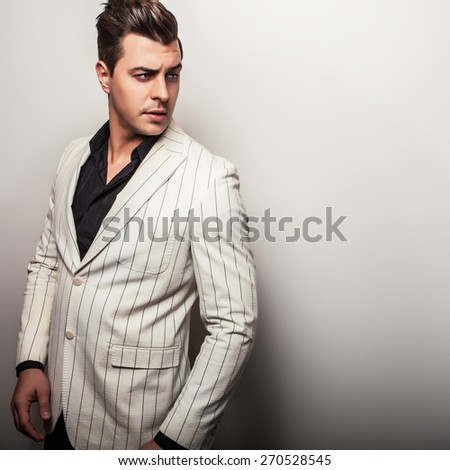Elegant young handsome man in white costume. Studio fashion portrait.
