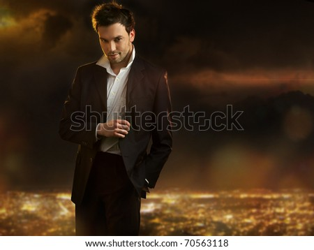 Elegant young handsome man over night city background - stock photo