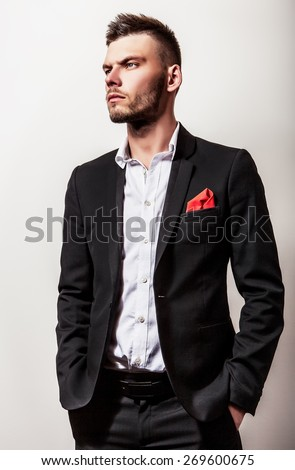 Elegant young handsome serious man in black costume. Studio fashion portrait.  - stock photo