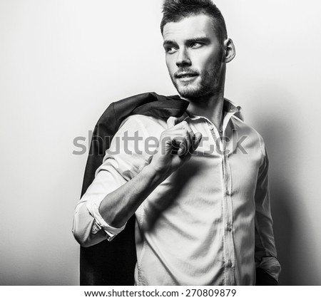Elegant young handsome serious man in white shirt with jacket. Black-white studio fashion portrait. - stock photo
