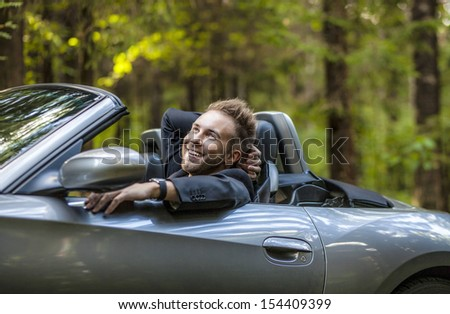 Elegant young happy man in convertible car outdoor.