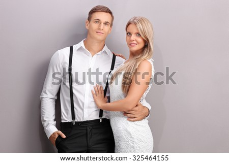 Elegant young man and woman hugging and posing against a gray wall - stock photo