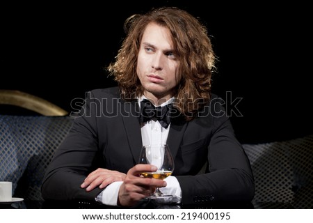 Elegant young man holding a glass of brandy looking away, dark background. - stock photo