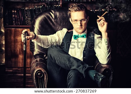 Elegant young man in a suit sitting in armchair and smoking a cigar. Vintage room. Fashion. - stock photo