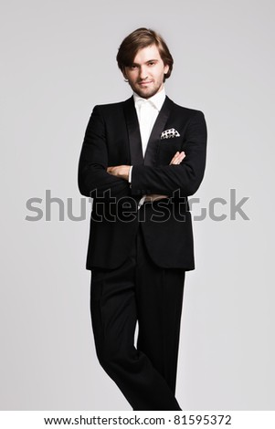 elegant young man in black tuxedo, portrait, studio shot - stock photo