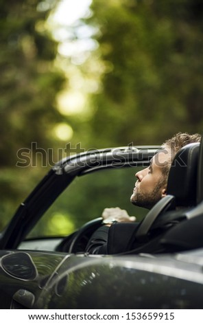 Elegant young man in convertible car looking up. Outdoor photo. - stock photo