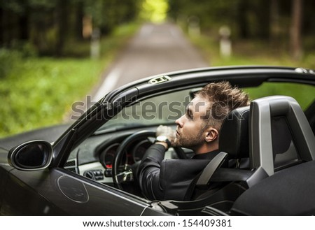 Elegant young man in convertible car outdoor.  - stock photo