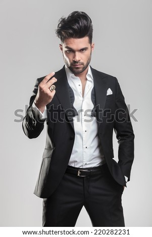 Elegant young man in tuxedo looking at the camera while snapping his finger and holding one hand in his pocket.  - stock photo