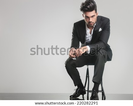 Elegant young man in tuxedo sitting on a stool while holding his finger, looking at the camera.  - stock photo