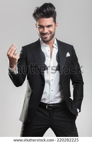 Elegant young man in tuxedo snapping his finger while smiling for the camera, holding one hand in the pocket. On grey background. - stock photo