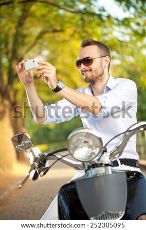 Elegant young man on classic motorbike making a break to take some photos of a beautiful surrounding nature. - stock photo