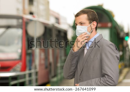 elegant young man walking wearing a mask in city street concept of polllution - stock photo