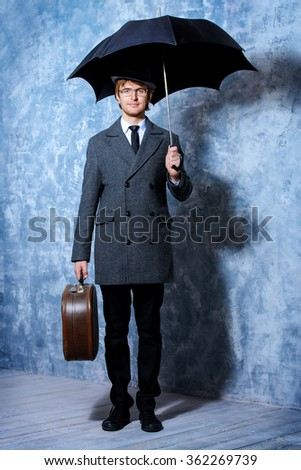 Elegant young man wearing classic hat and a coat stands with his black umbrella. Beauty, fashion. - stock photo