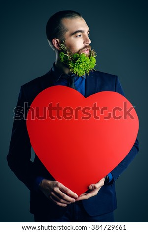 Elegant young man with a beard of green flowers holding red heart. Love concept. Valentine's Day. Barbershop. - stock photo