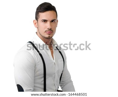 Elegant young man with white shirt and suspenders, on dark background, serious, confident - stock photo