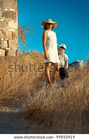 Elegant young mother and her cute little son walking outdoors on a summer day - stock photo