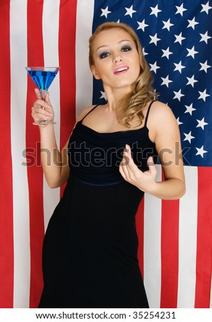 Elegant young sexy woman with cocktail against the american flag
